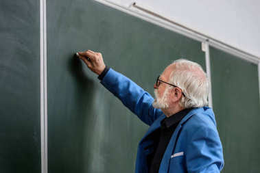 side view of senior lecturer writing something on blackboard with piece of chalk