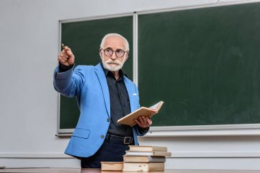 senior lecturer holding book and pointing on something