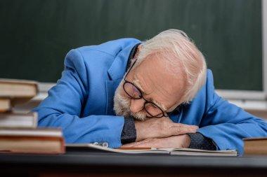 senior lecturer sleeping at working table