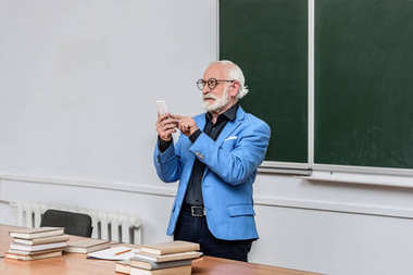grey hair professor looking at smartphone in lecture room