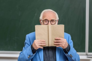 grey hair professor looking out from book