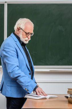 grey hair professor looking at book