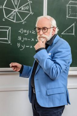 pensive grey hair professor standing at blackboard with piece of chalk