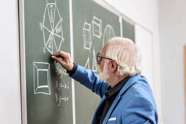 side view of grey hair professor drawing with piece of chalk at blackboard