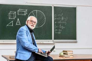 smiling grey hair professor sitting on table with laptop