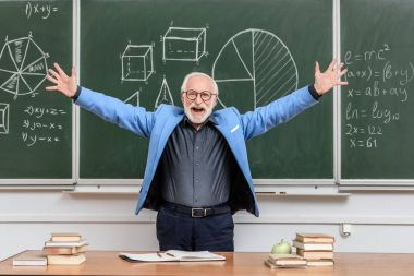 happy senior lecturer with open arms standing near blackboard