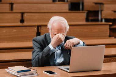 tired grey hair professor touching nose bridge