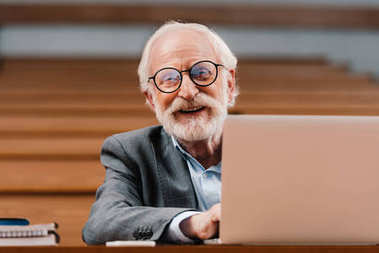 smiling grey hair professor sitting in empty lecture room with laptop