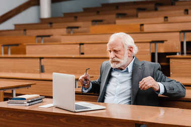 grey hair professor sitting in empty lecture room and looking at laptop