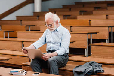 grey hair professor sitting on desk in empty lecture room and using laptop