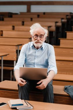 senior lecturer in empty lecture room holding laptop and looking at camera