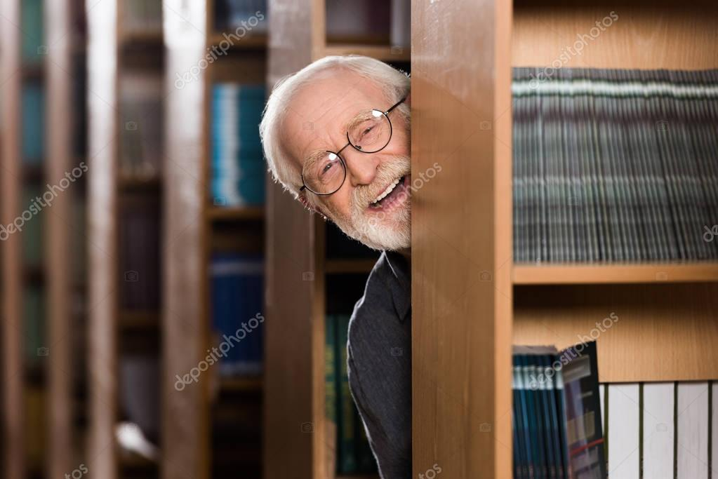happy grey hair librarian looking out from shelf