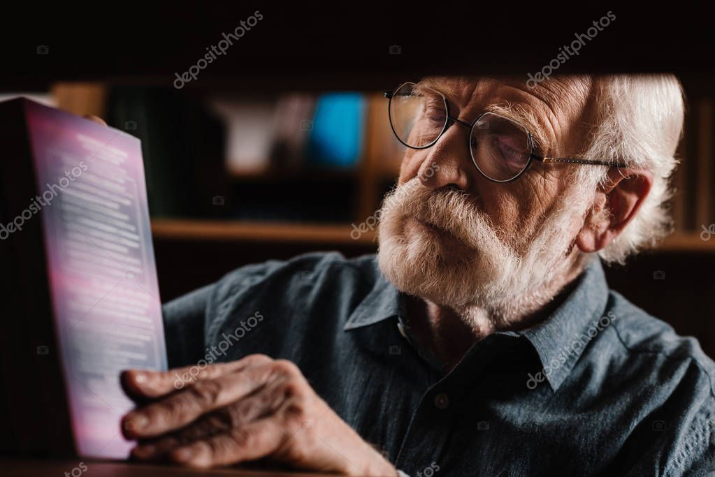 grey hair librarian looking at book on shelf
