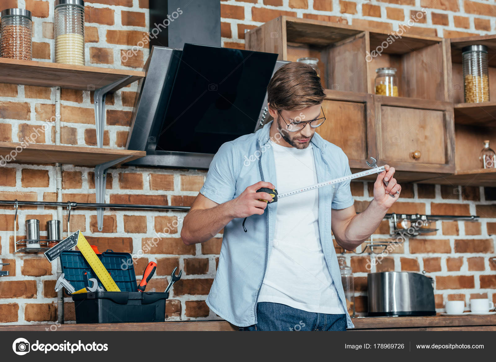 Junger mann mit maßband während der reparatur dunstabzugshaube