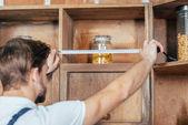 Selektivní fokus mladý údržbář měření kuchyňského nábytku s páskou