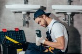 Photo young professional plumber fixing sink in bathroom