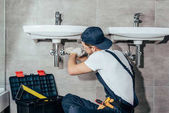 Photo back view of young professional plumber fixing sink in bathroom