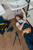 Photo high angle view of young male plumber fixing sink in bathroom