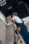 Fotografie nízký úhel pohledu instalatér práce s kanály v koupelně