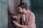 young man repairing door lock with screwdriver and flashlight