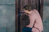 young repairman checking door lock with flashlight