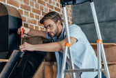 handsome young man in eyeglasses repairing kitchen hood with screwdriver