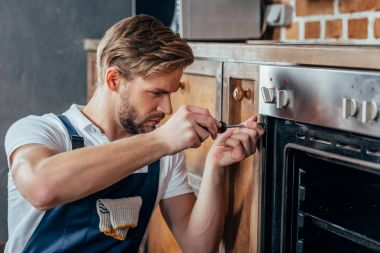 handsome young repairman fixing oven with screwdriver