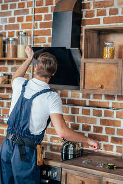 back view of young handyman fixing extractor hood in kitchen