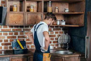 young handyman standing with hands on waist and looking at sink in kitchen