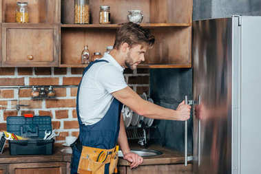 side view of handsome young repairman fixing refrigerator