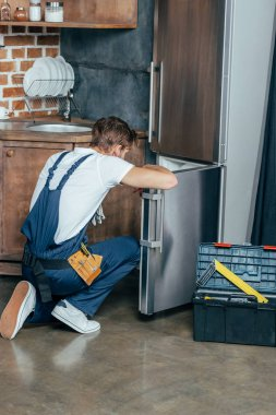back view of repairman in protective workwear fixing refrigerator in kitchen