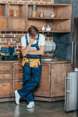 pensive young repairman looking at broken refrigerator in kitchen