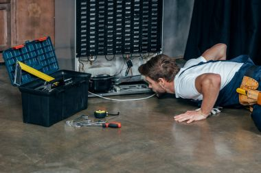young handyman in protective workwear with toolbox looking at broken refrigerator