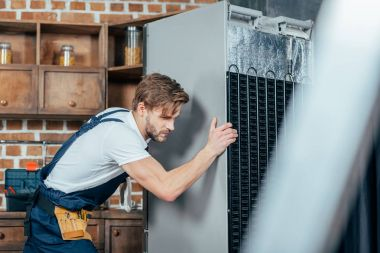 young repairman in protective workwear moving refrigerator in kitchen