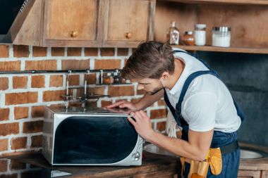 professional young handyman repairing microwave oven in kitchen