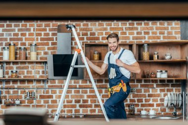 selective focus of young foreman standing on ladder and smiling at camera while fixing kitchen hood