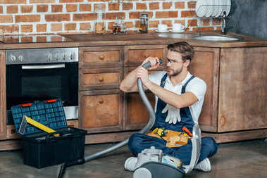 young repairman in protective glasses checking broken vacuum cleaner