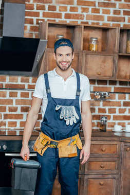 professional home master with toolbox and tool belt smiling at camera