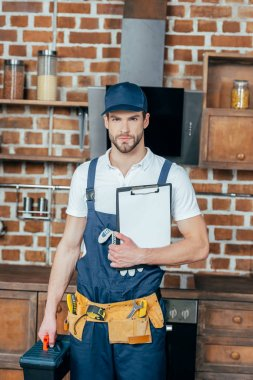 professional home master with toolbox and clipboard looking at camera