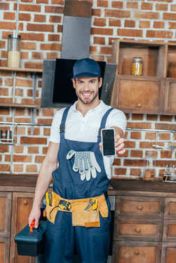 smiling young home master holding smartphone and toolbox