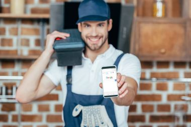 smiling young home master holding smartphone with google website