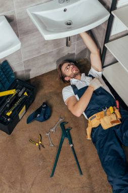 high angle view of young male plumber fixing sink in bathroom
