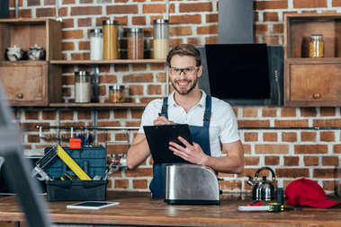 young repairman writing on clipboard and smiling at camera while fixing toaster
