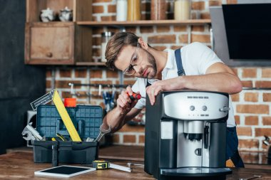 professional young repairman in eyeglasses fixing coffee machine