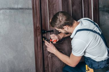 young repairman fixing door lock with screwdriver