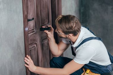 young manual worker in overall checking door lock with flashlight