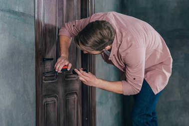 young man repairing wooden door with flashlight and measuring tape