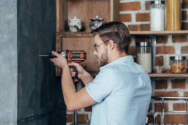 side view of young man drilling wall with electric drill at home