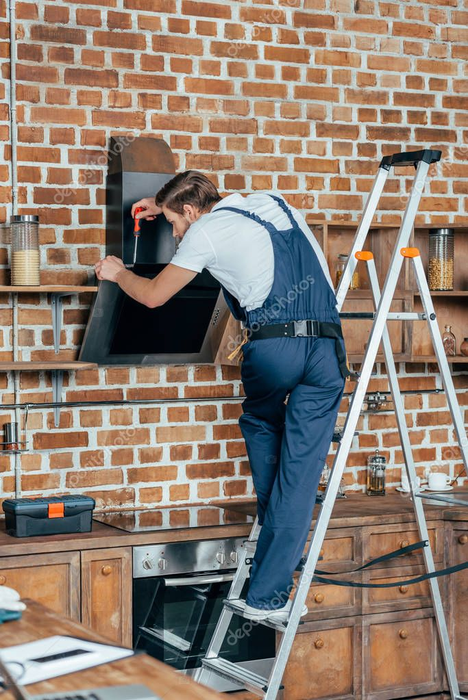 professional young foreman standing on ladder and fixing kitchen hood with screwdriver