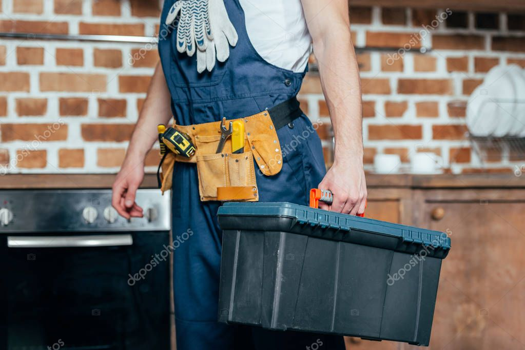 cropped shot of home master with tool belt holding toolbox